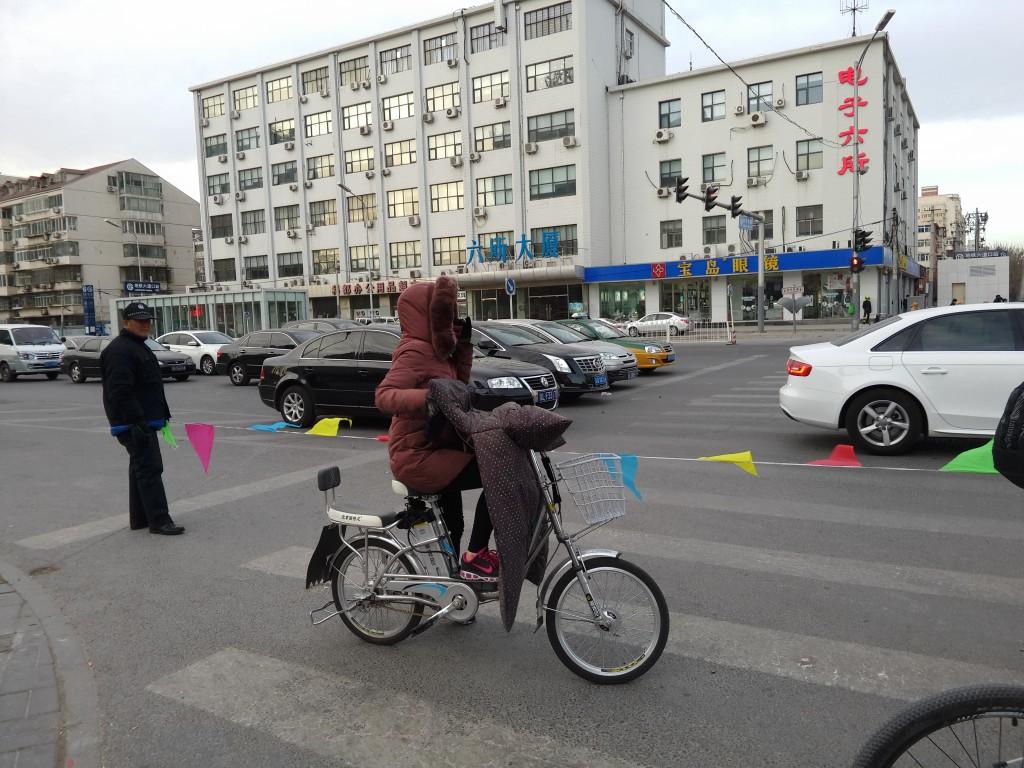 Die bunten Fähnchen halten die Dame in Braun heldenhaft davon ab, bei Rot die Straße zu überqueren