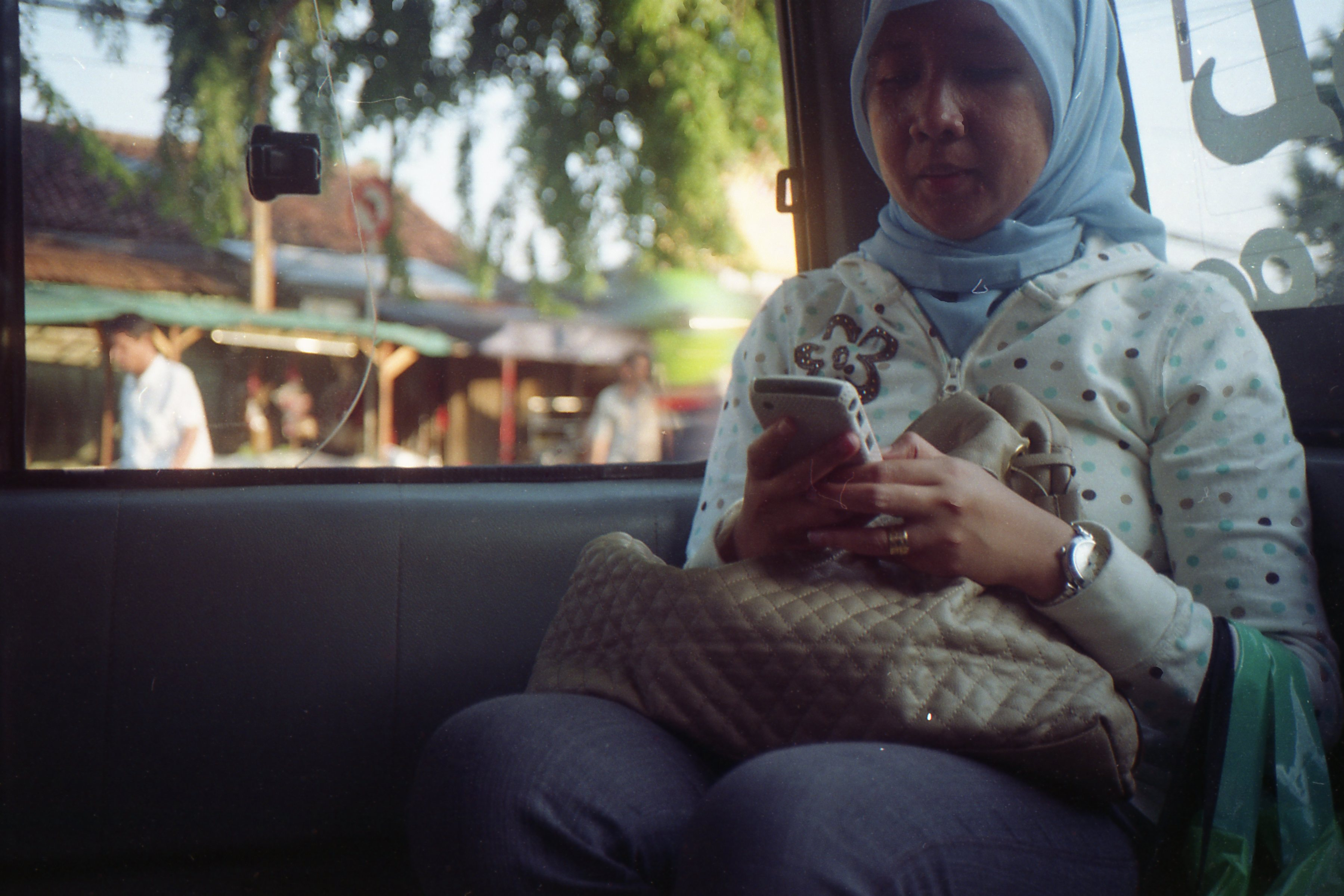 Eine Frau sitzt im Bus und nutzt ihr Handy